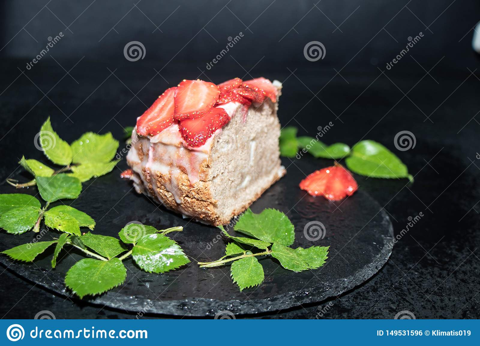 Biscuit cake with sour cream decorated with strawberries, fresh berry on a tray, with blue lights in the background,