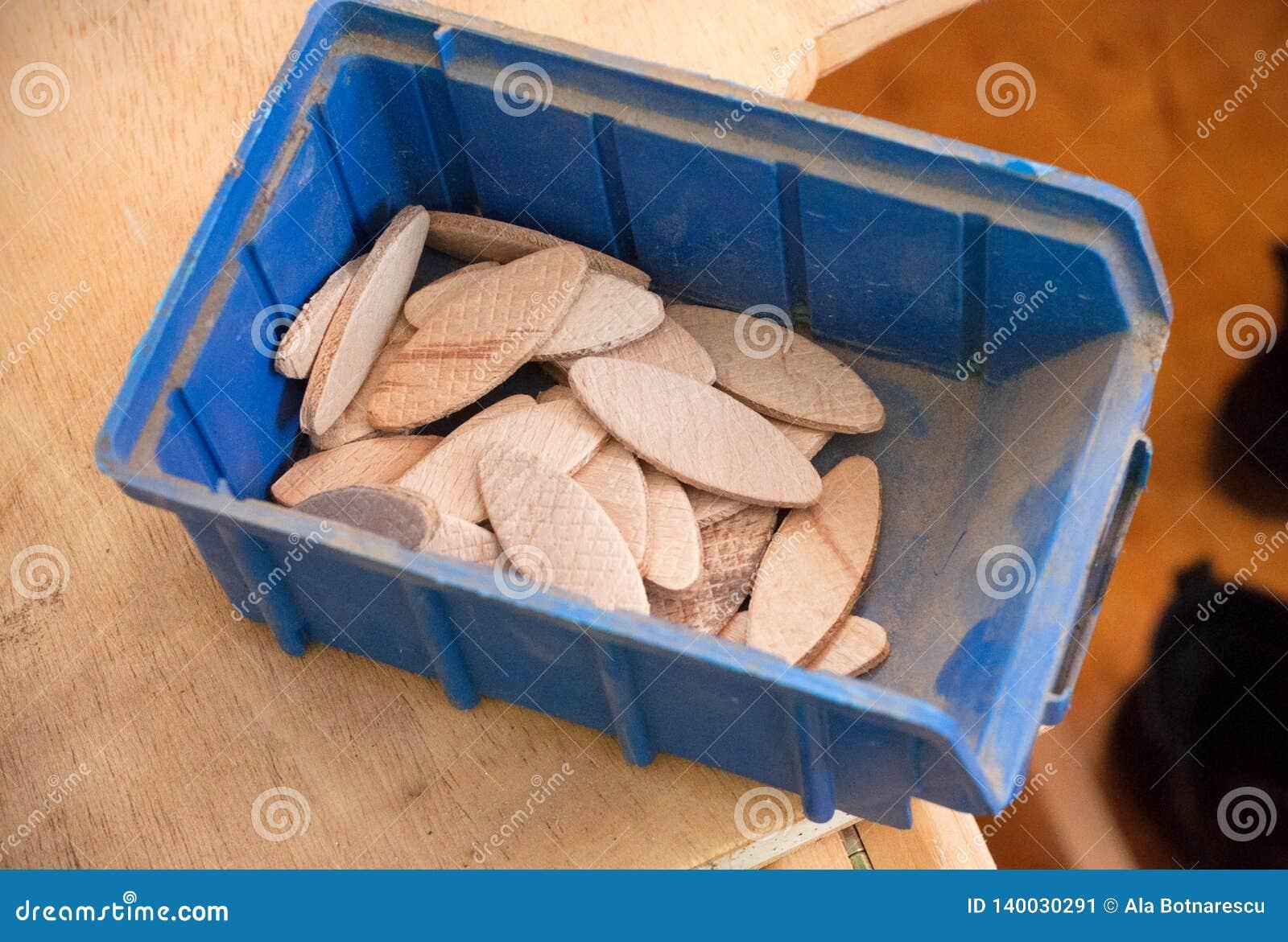 Biscuit comprimé en bois de hêtre dans un récipient en plastique bleu