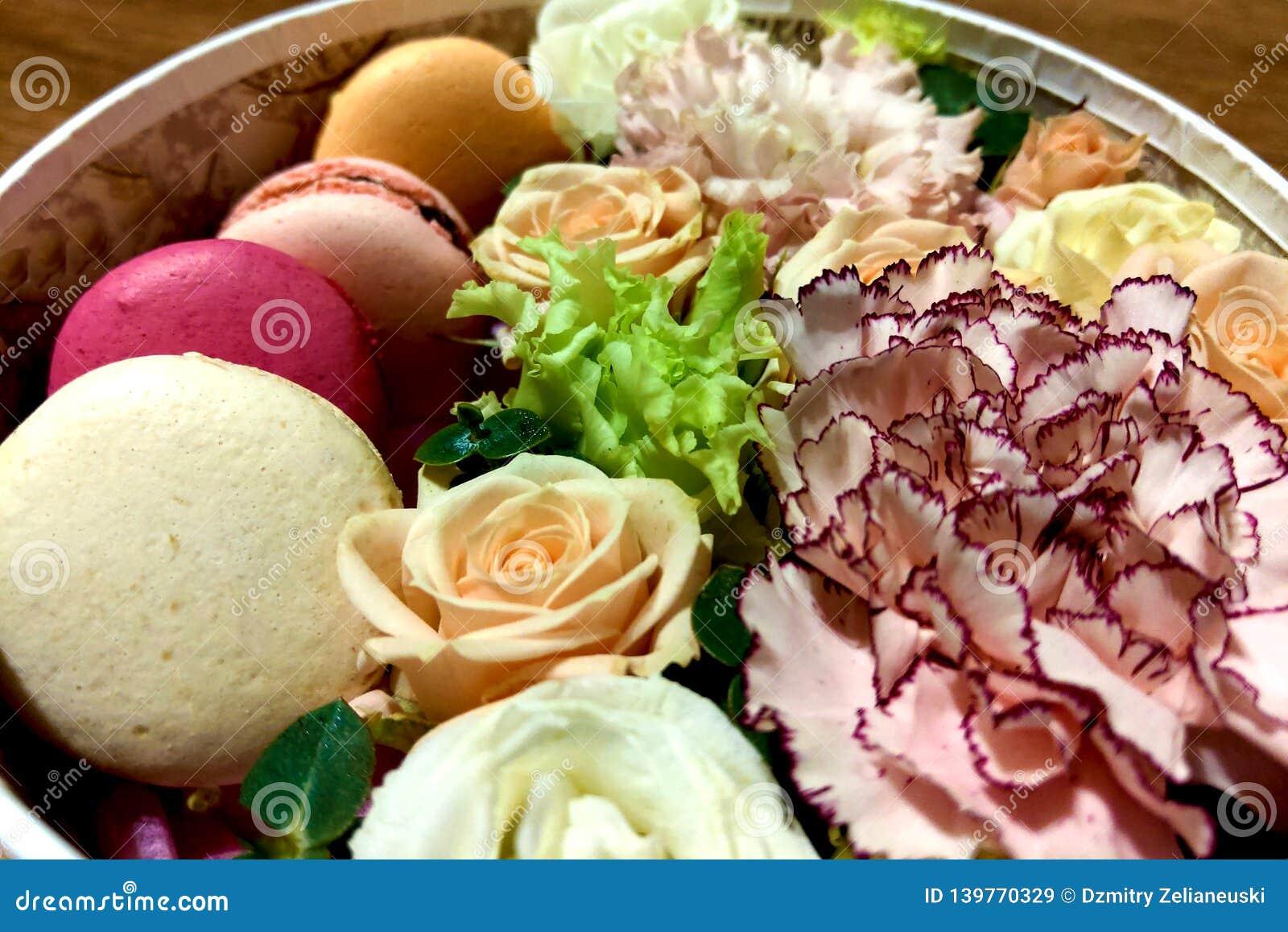 Biscuits colorés délicieux de macarons dans un boîte-cadeau avec le bouquet de floraison de fleur des roses, mattiola, oeillets