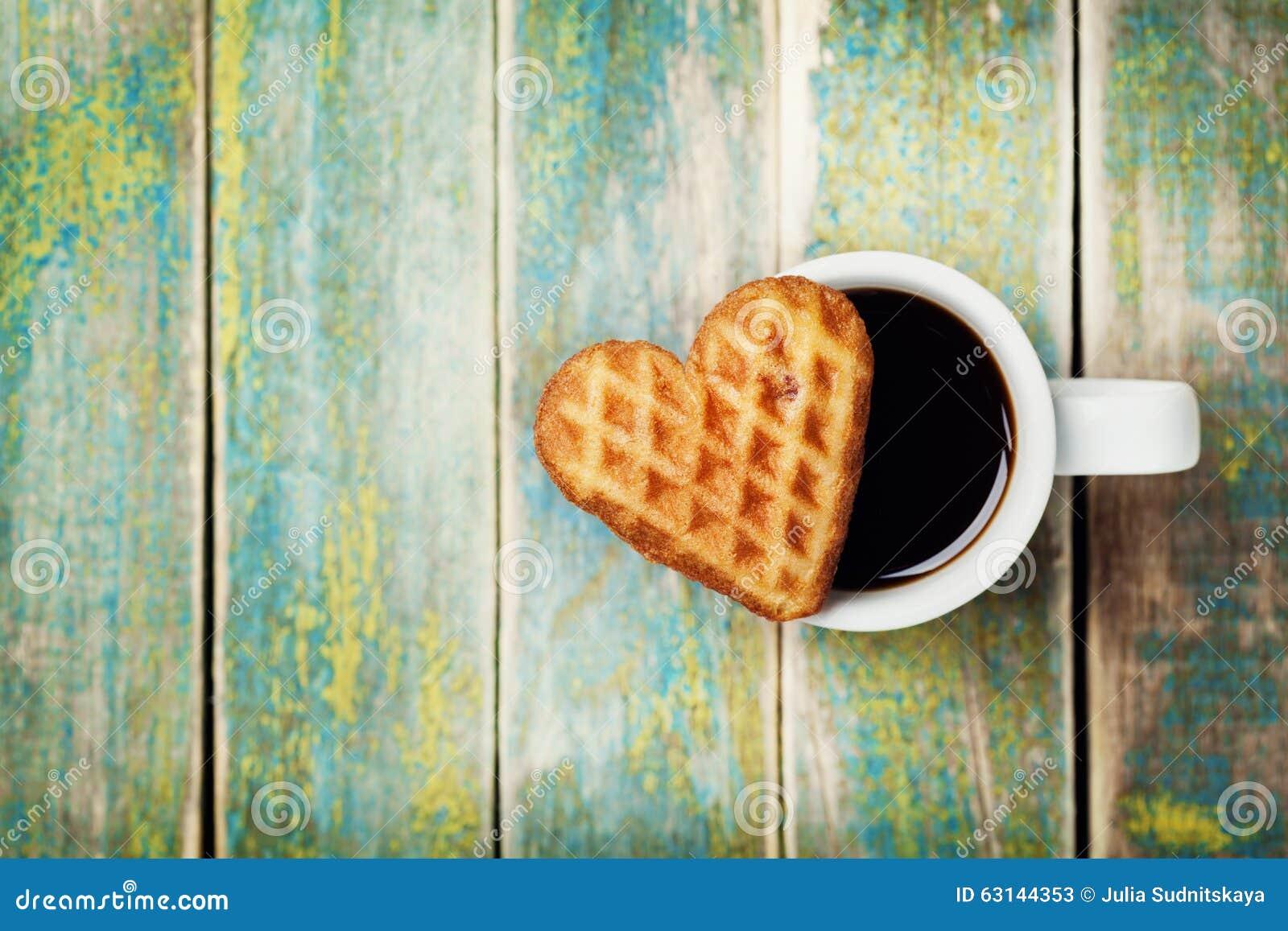 Biscuits de gaufre dans la forme du coeur avec la tasse de café sur le fond en bois pour le jour de valentines