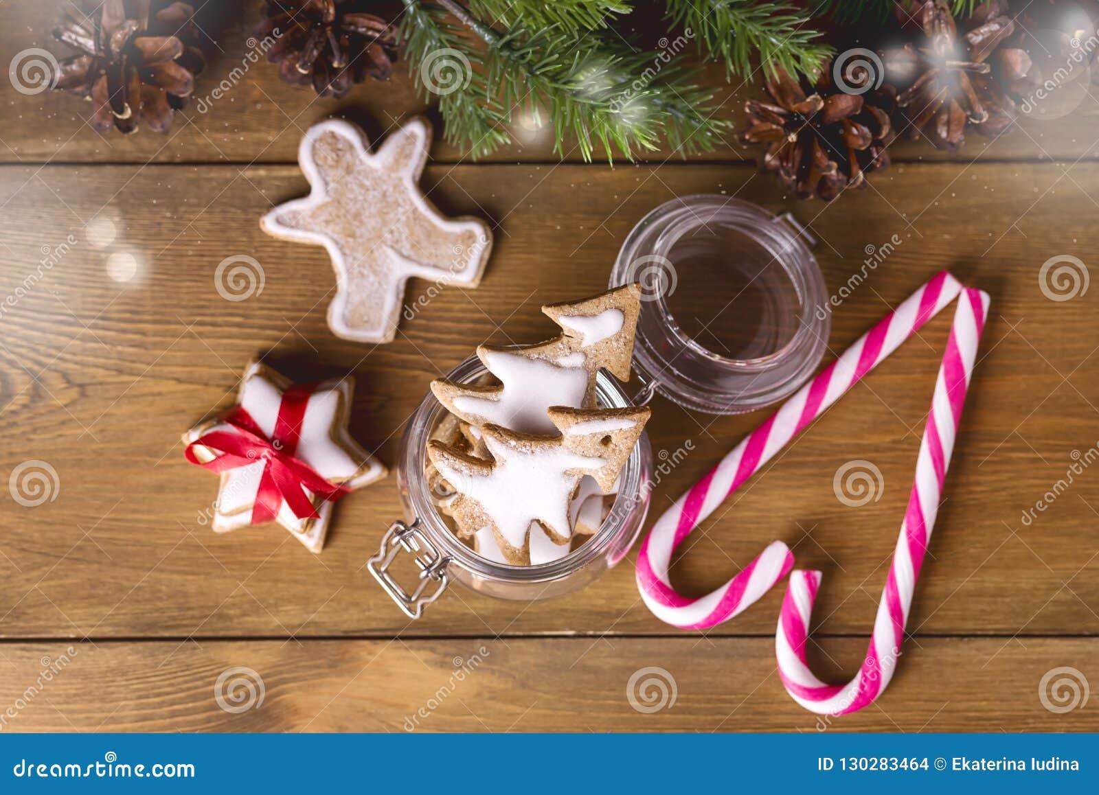 Biscuits faits maison de pain d épice en sucrerie de fête Cane Lights Wooden Background de carte de voeux de pot de Noël de vacan