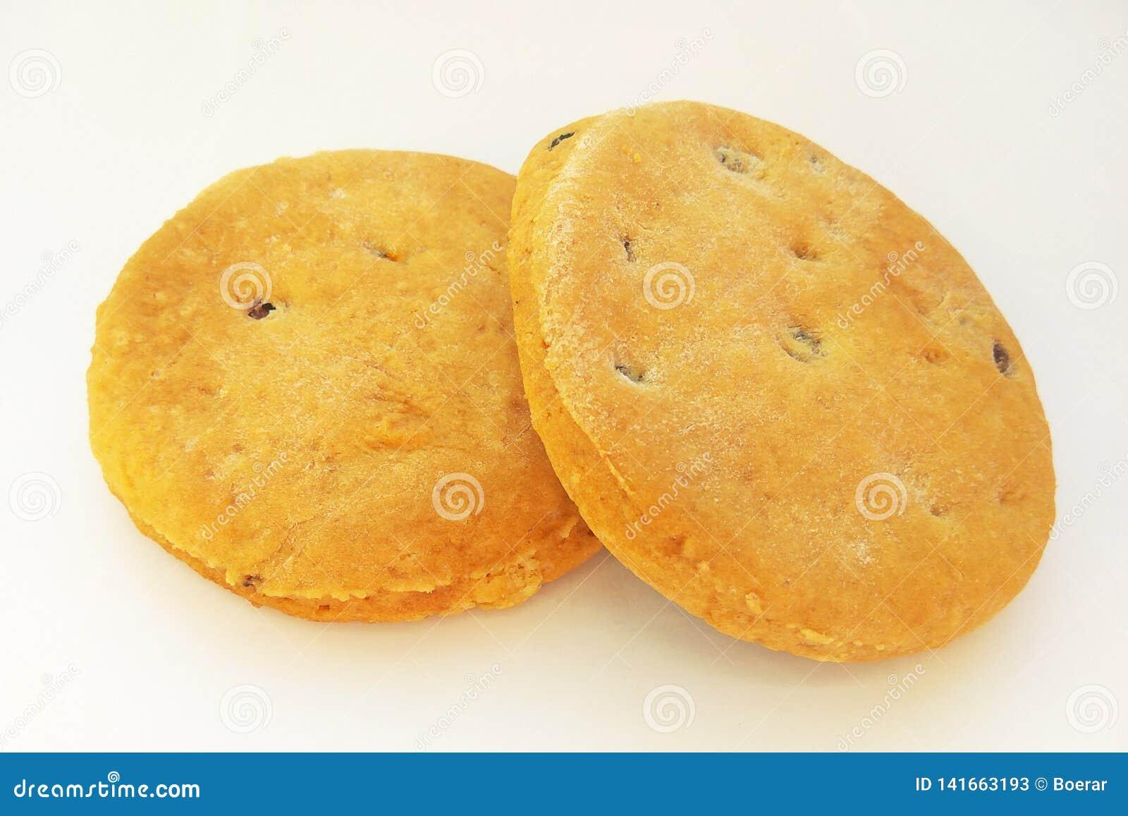 Biscuits faits maison fraîchement cuits au four avec des raisins secs sur le fond blanc