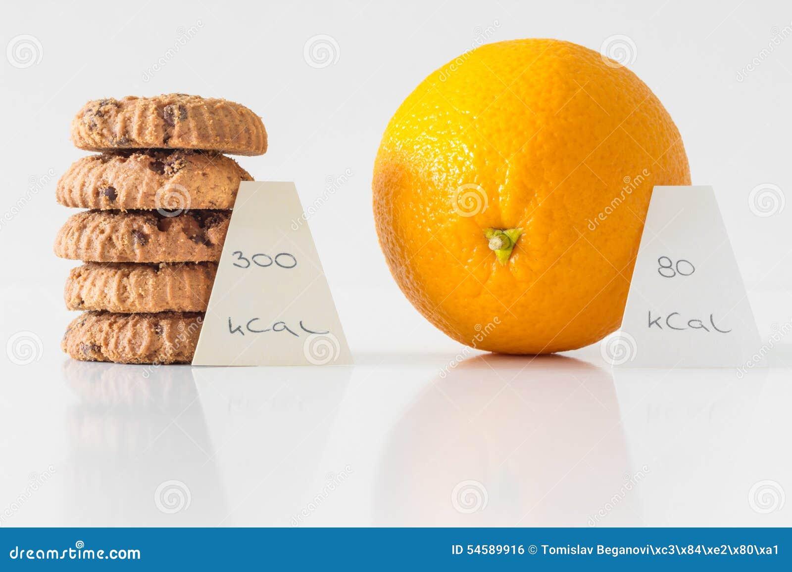Biscuits ou fruit orange, concept bien choisi de régime, compte de calorie