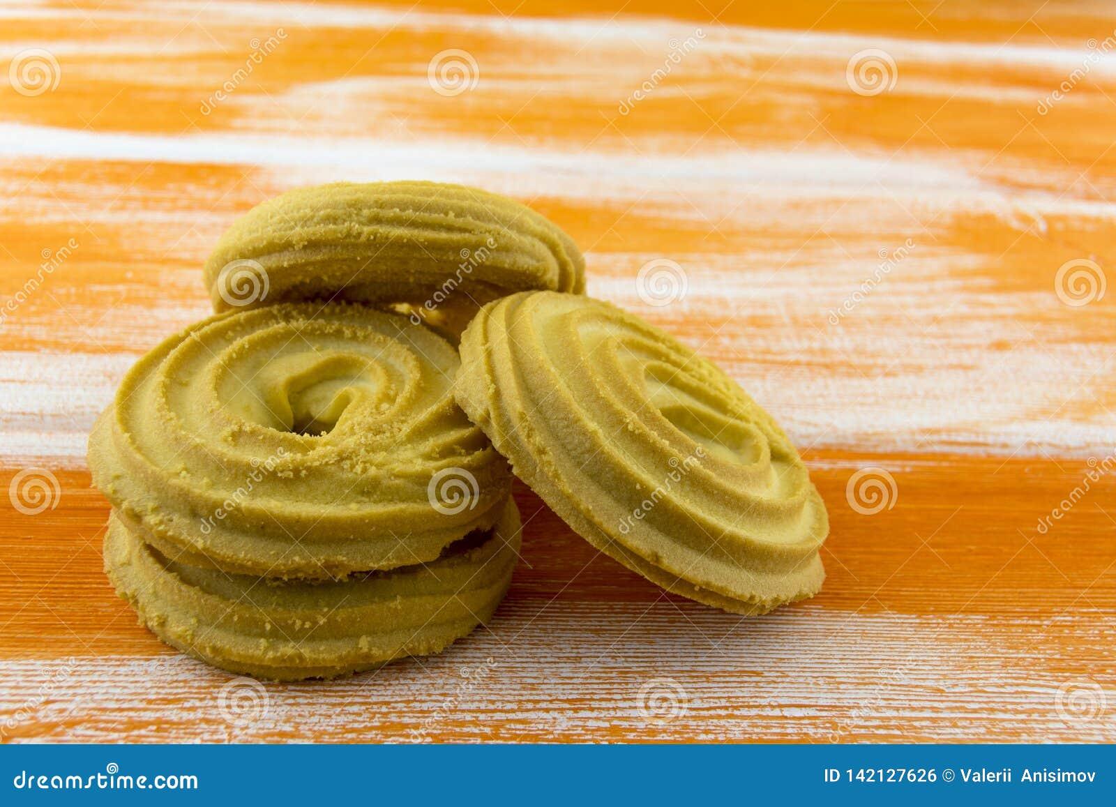 Biscuits sablés ronds se trouvant sur une table orange en bois