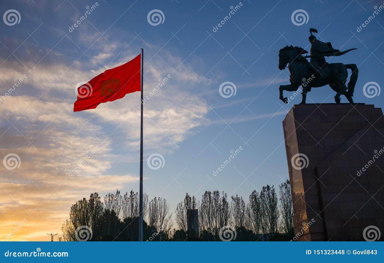 Bishkek Kirgizistan: Monument för Manas, hjälte av forntida kyrgyz epos, samman med nationell Kirgizistanflagga på Bishkek centra