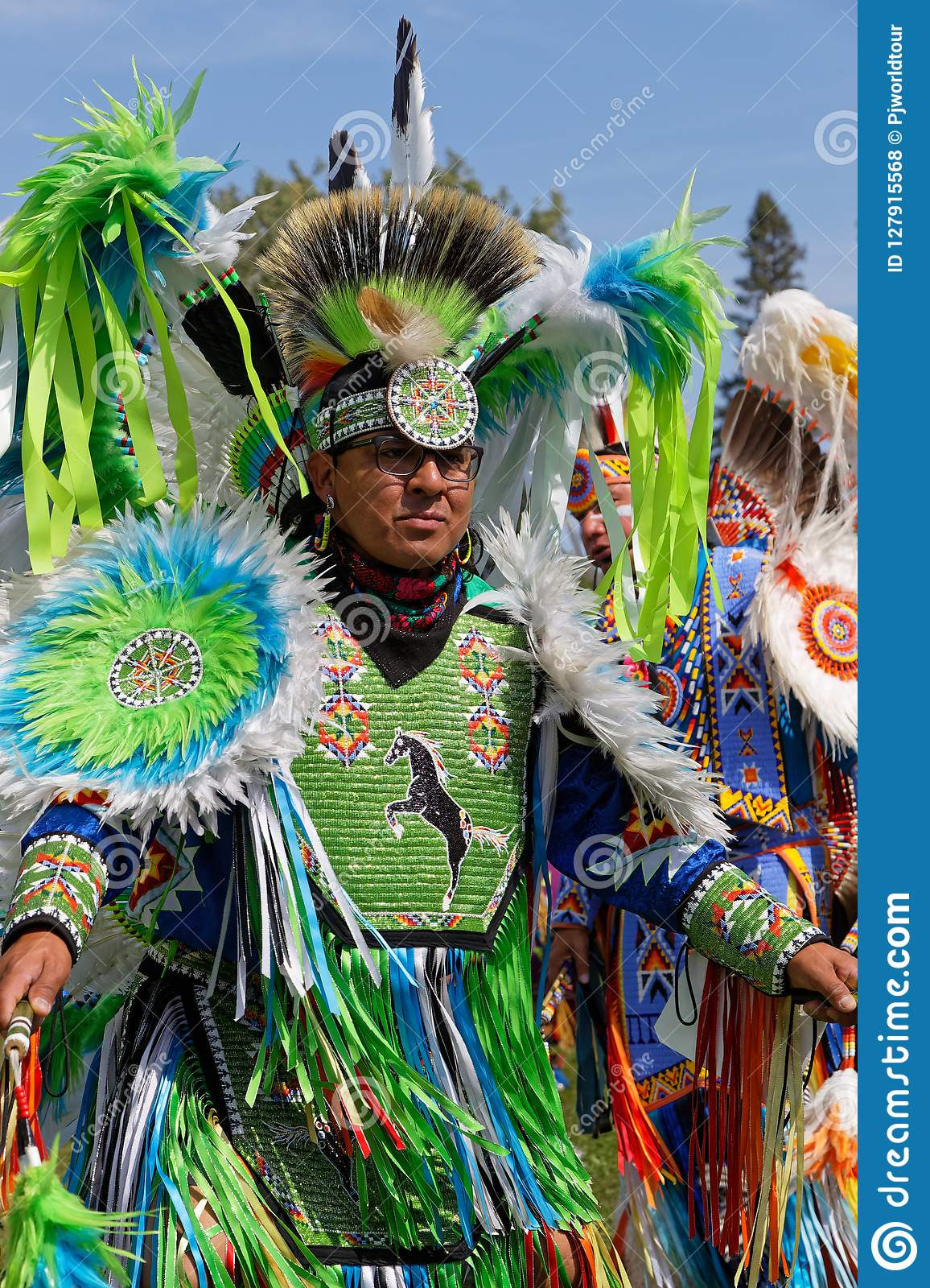 A fancy dancer dressed in green at the Pow Wow