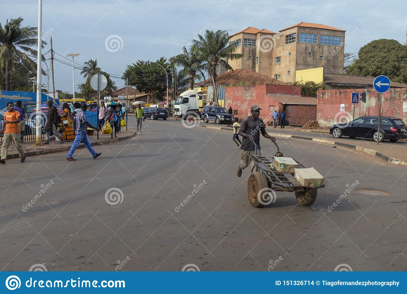 Street scene in the city of Bissau with people crossing a street near the Bandim Market, in Guinea-Bissau