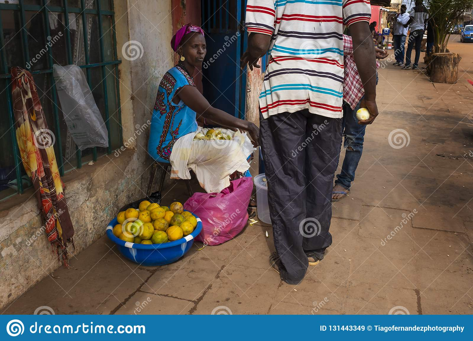 Street scene in the city of Bissau with a woman selling oranges, in Guinea-Bissau, West Africa