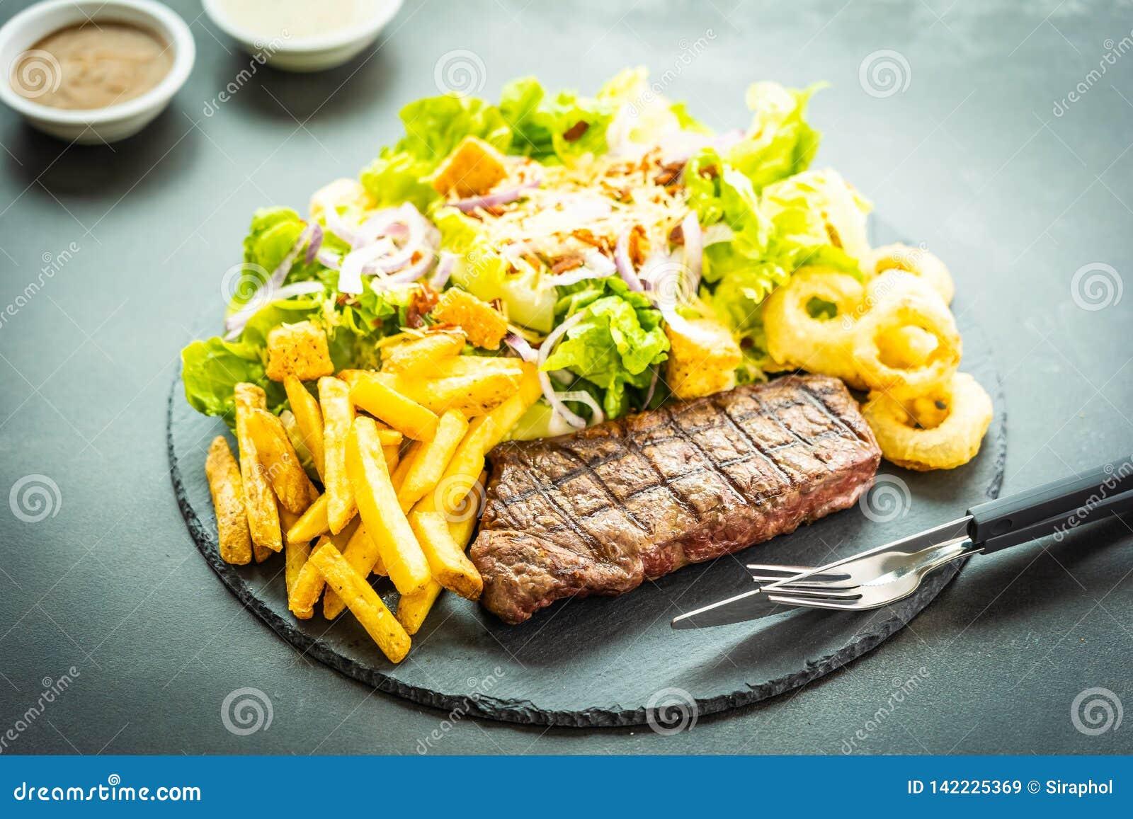 Bistecca arrostita della carne del manzo con l anello di cipolla delle patate fritte con salsa e la verdura fresca