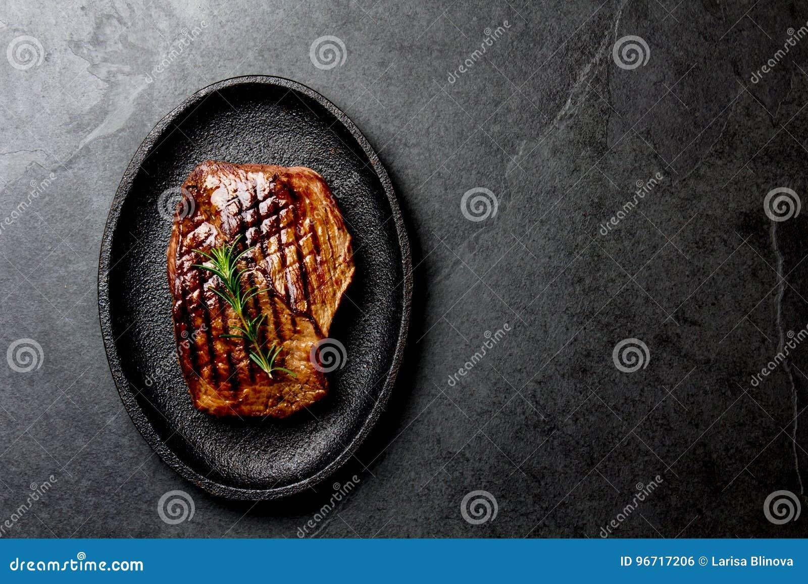 Bistecca di manzo arrostita sul piatto nero del ghisa Fondo con lo spazio della copia Barbecue, filetto di manzo della carne del