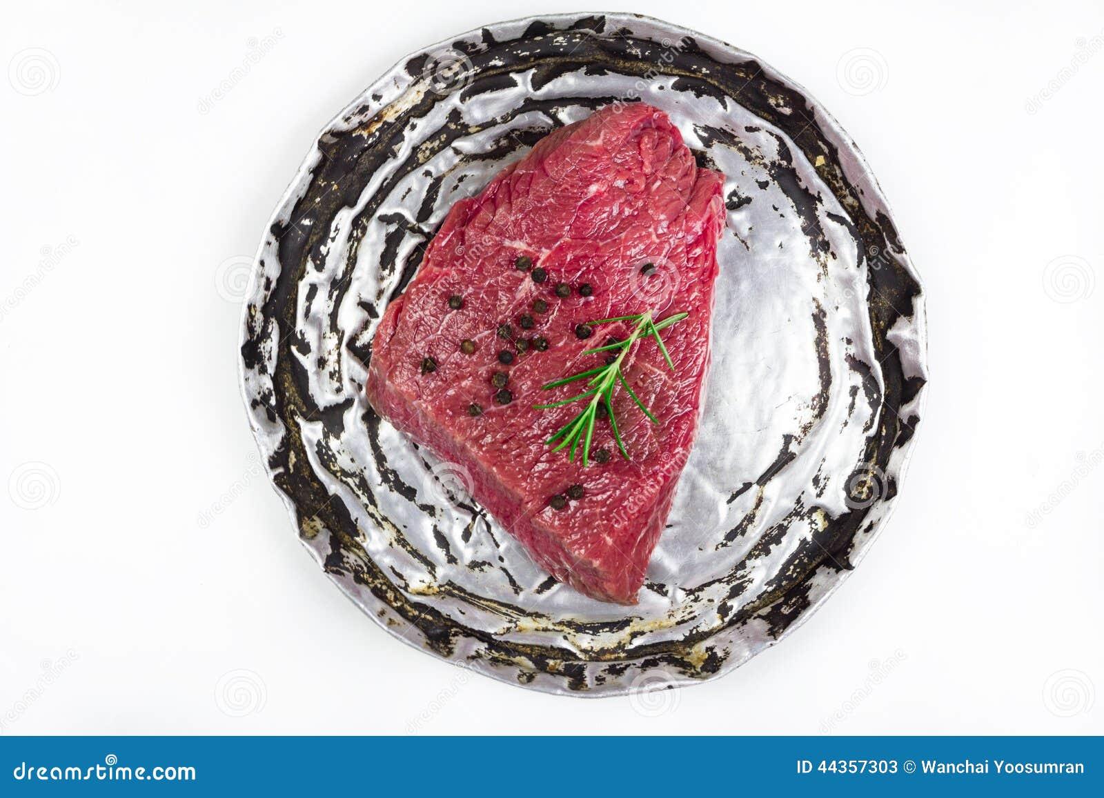 Bistecca di manzo cruda sul vecchio piatto