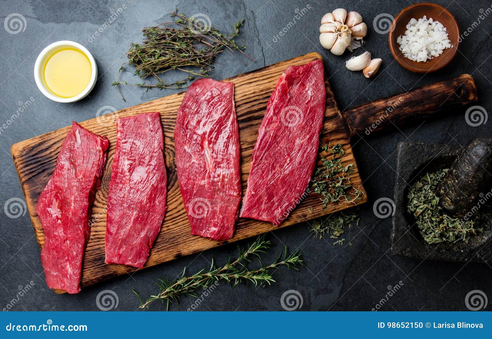 Bistecche di manzo fresche della carne cruda Filetto di manzo sul bordo di legno, spezie, erbe, olio sul fondo di gray di ardesia