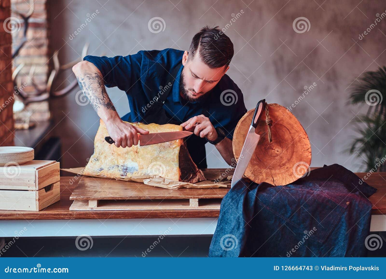 Bitande exklusivt knyckigt kött för kockkock på tabellen i ett kök med vindinre