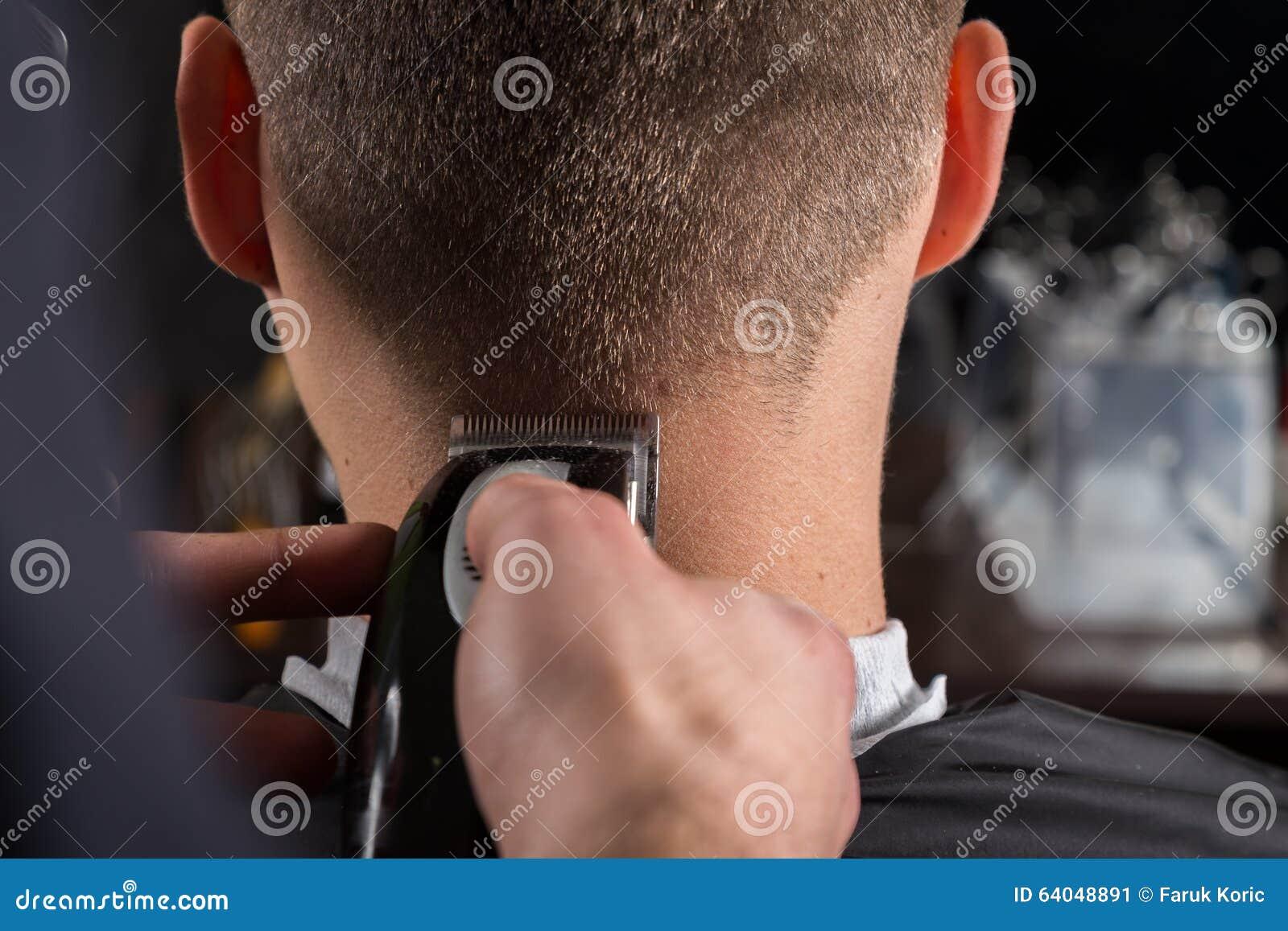 Bitande klienthår för frisör med en elektrisk hårclipper