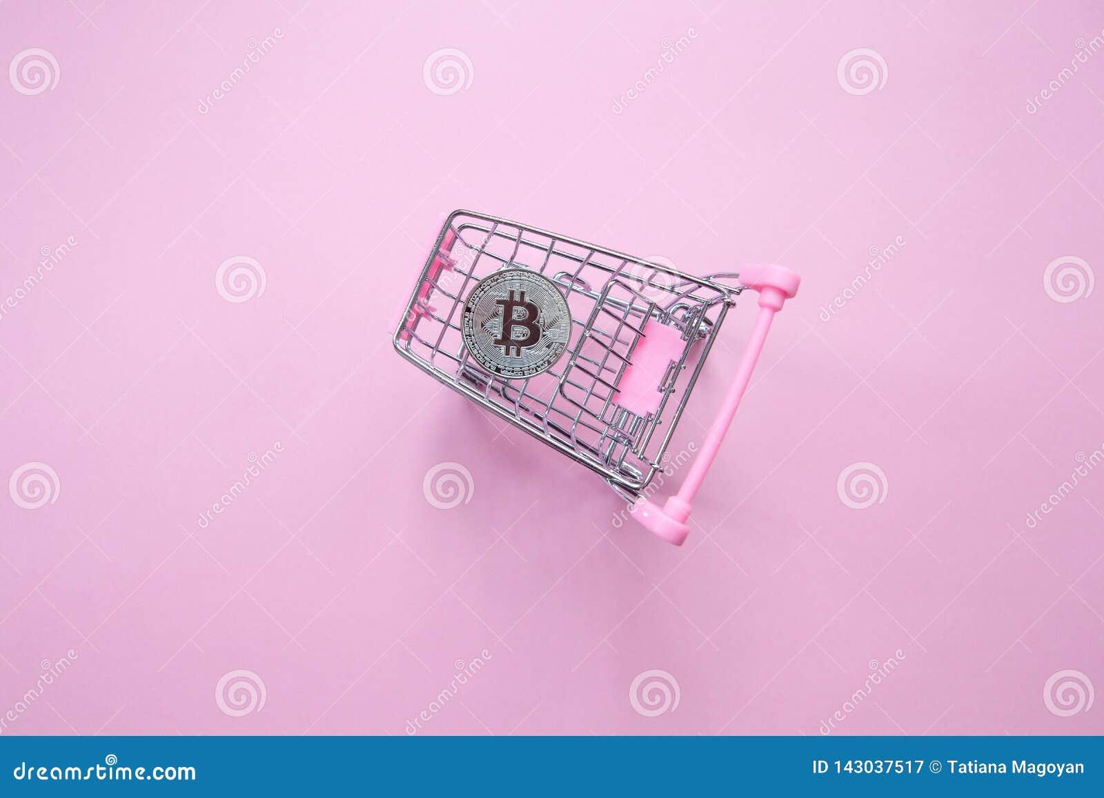 Bitcoin argenté dans le caddie sur un fond rose millénaire Vue supérieure minimalisme Orientation horizontale Configuration plate