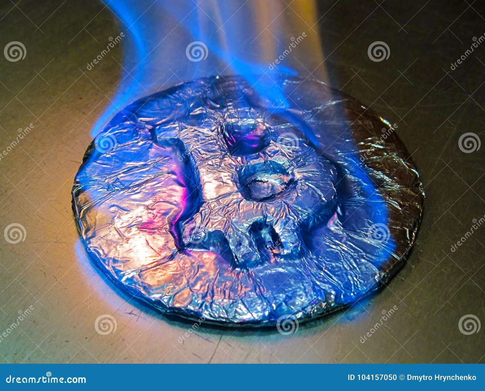 Bitcoin auf Feuer Wirkliche Münze brennt mit blauer Flamme als Symbol des heißen Preises oder des kritischen Falles