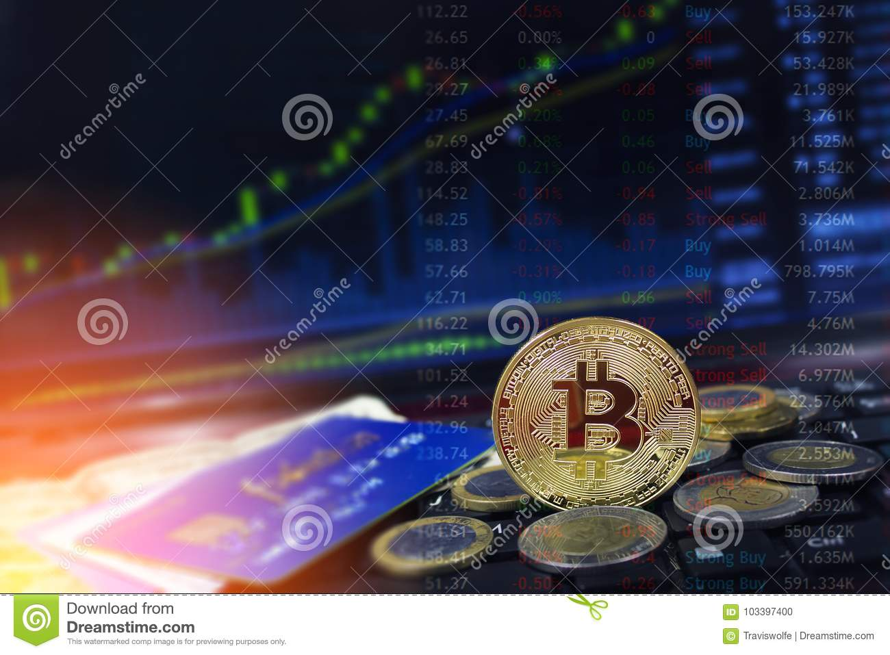 Bitcoin currency with credit cards and coins on laptop keyboard with rising price charts in the background.