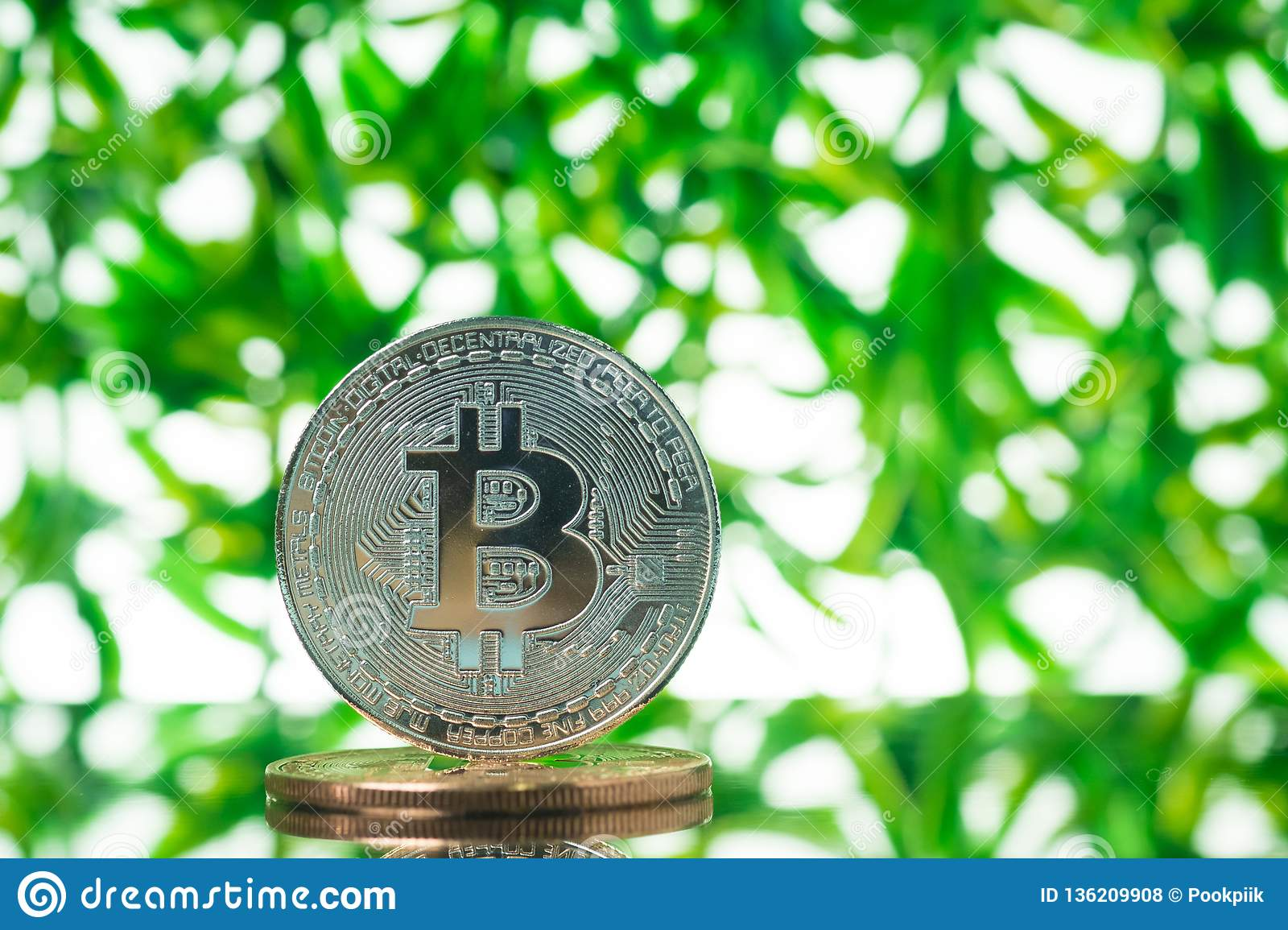 Bitcoin digital currency, bit-coin on green blurred bokeh background, Cryptocurrency money concept
