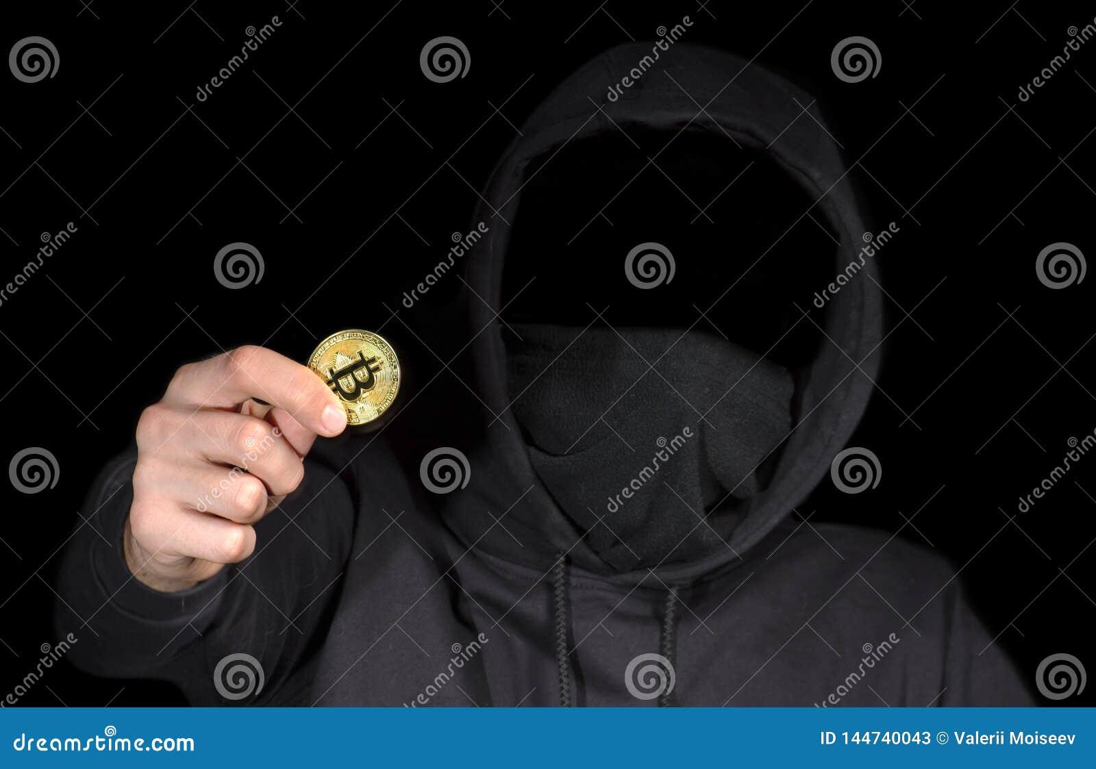 Bitcoin för Closeupen hackerhåll i handen som börjar cyberattack, begreppscybersäkerhet, på svart