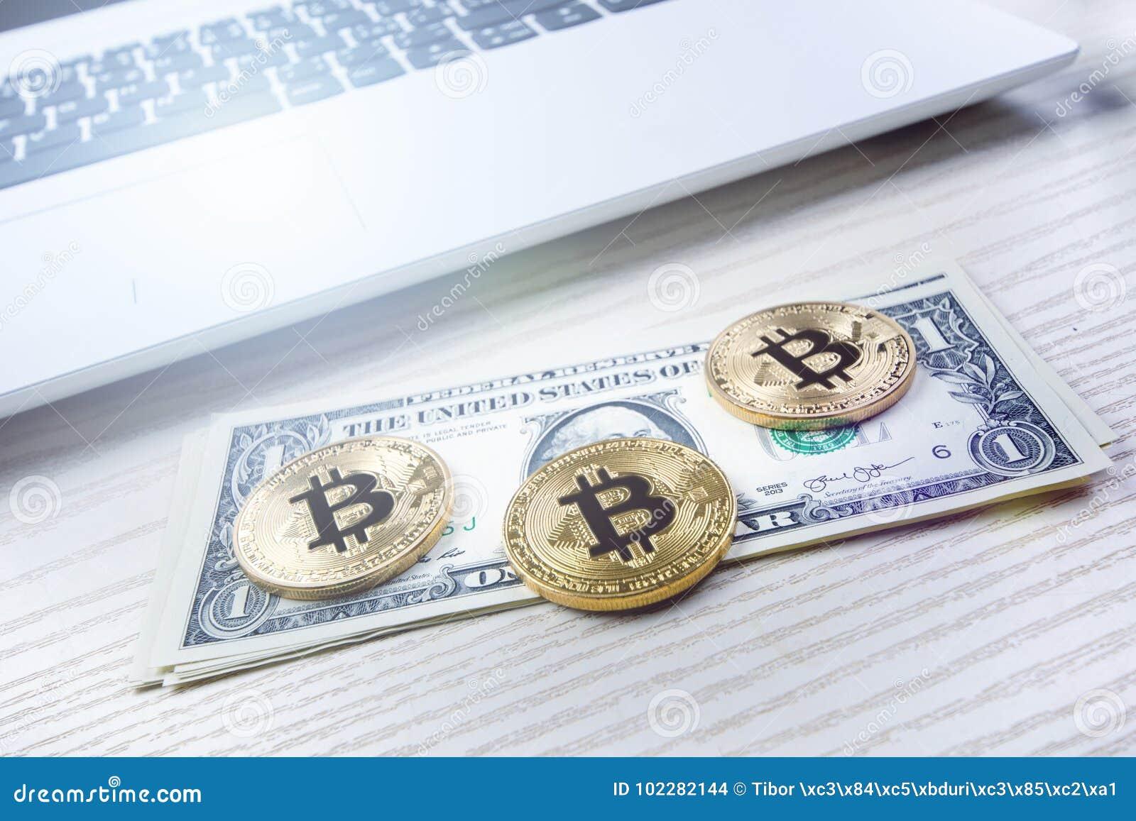 Bitcoin gouden muntstukken op een lijst met dollarbankbiljetten en laptop Virtueel Geld Cryptocurrencyzaken Bureauachtergrond