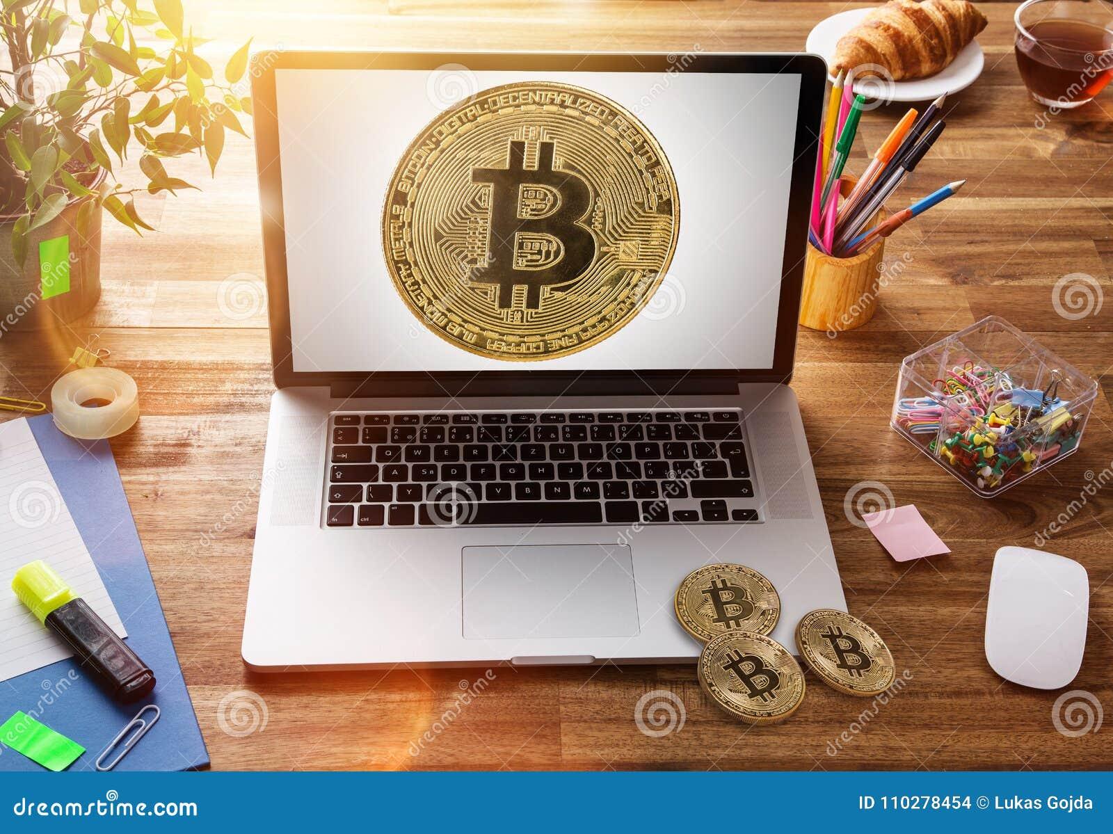Bitcoin guld- mynt med bärbara datorn på träkontorstabellen