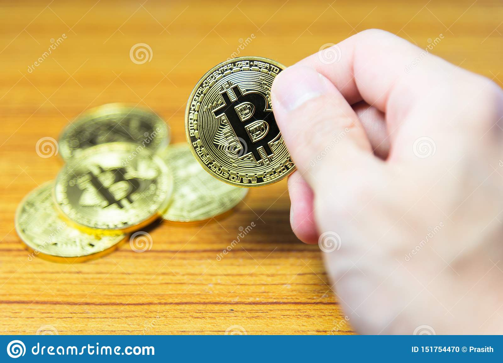 Bitcoin in hand with a blurred bitcoin background.