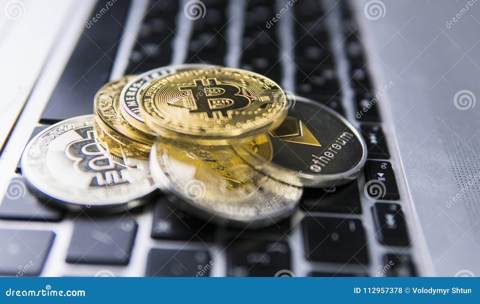 Bitcoin mynt på en överkant av andra crypto mynt på ett tangentbord av bärbara datorn Bitcoin guld- mynt Cryptocurrency investeri