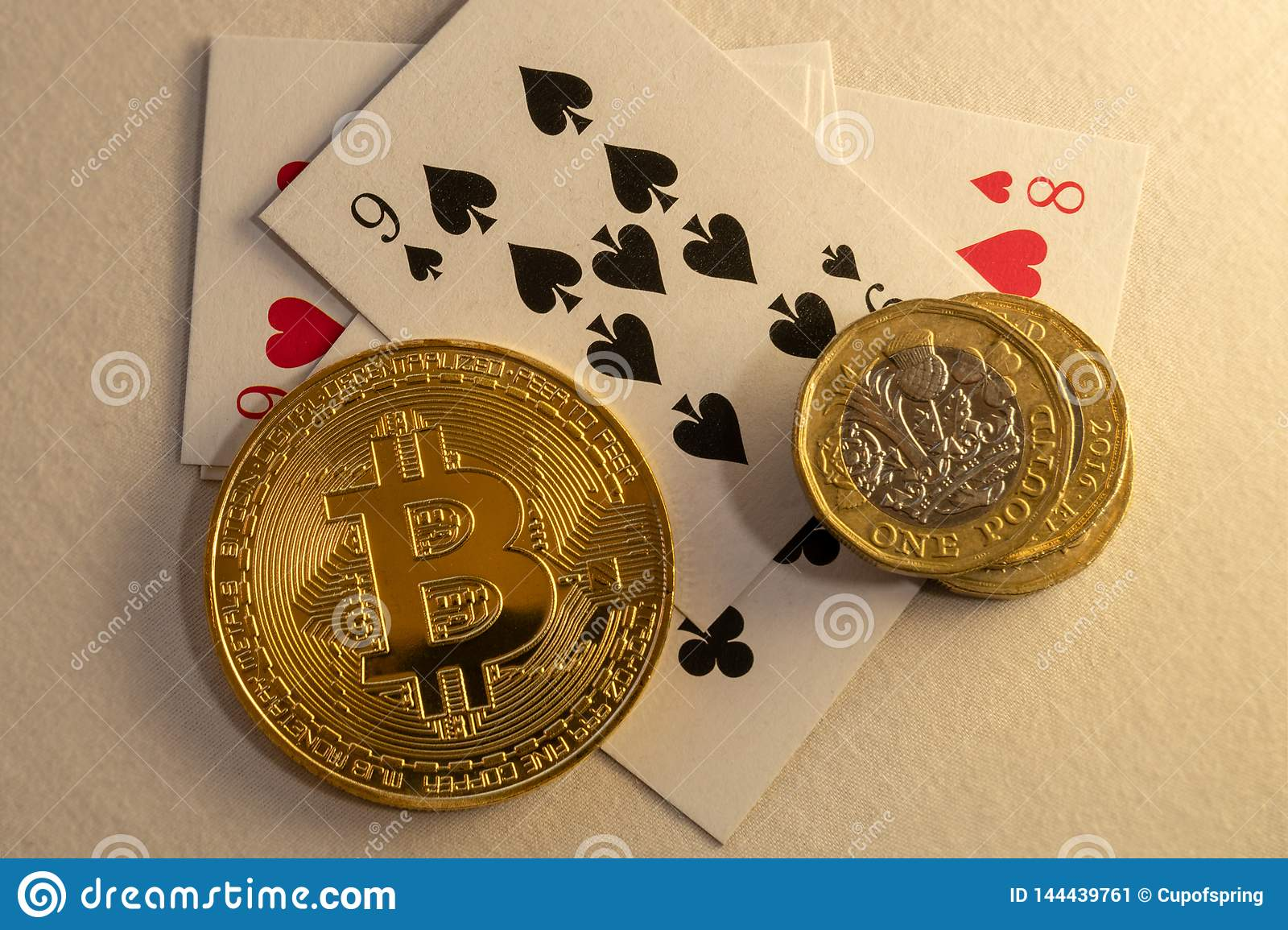 Bitcoins laying down on the table with bunch of coins and cards in the background. Online gambling concepts