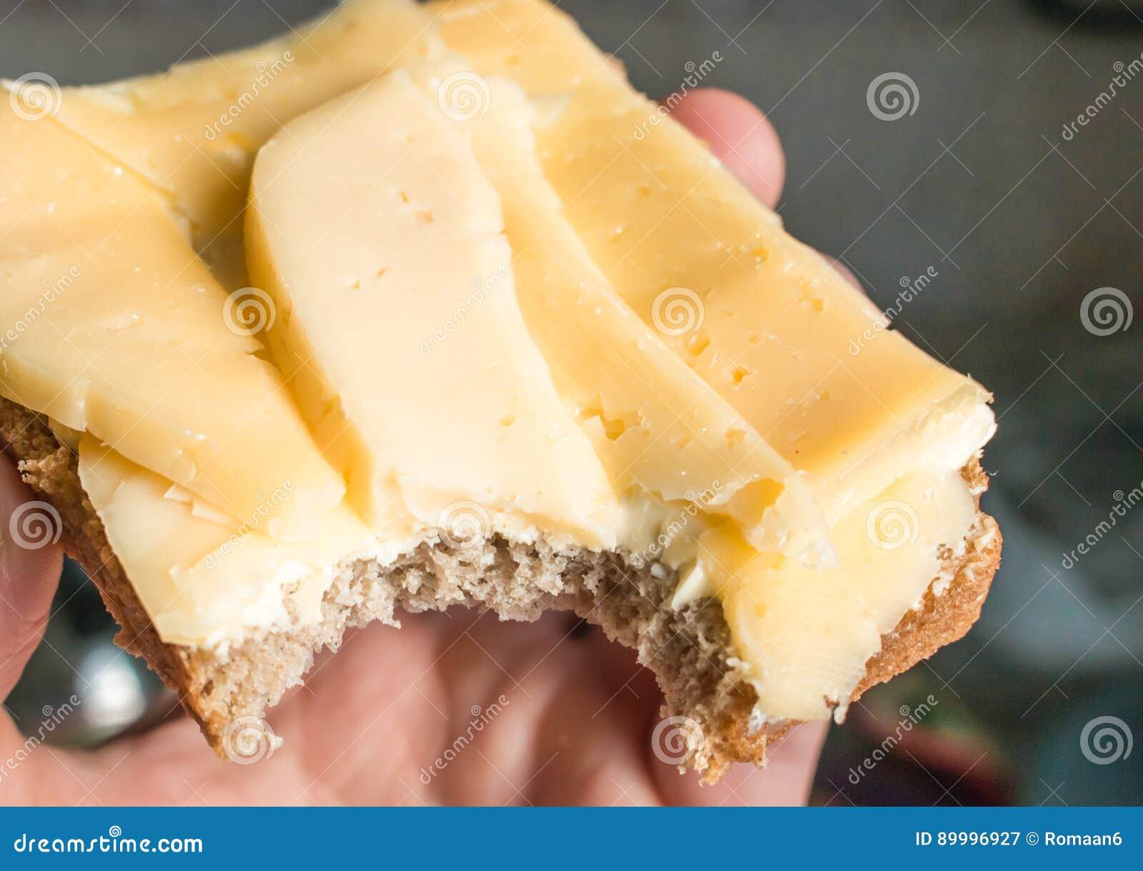 Biten smörgås som göras av rågbröd, smör och ost i en mans hand i strålarna av ett ljust morgonsolslut