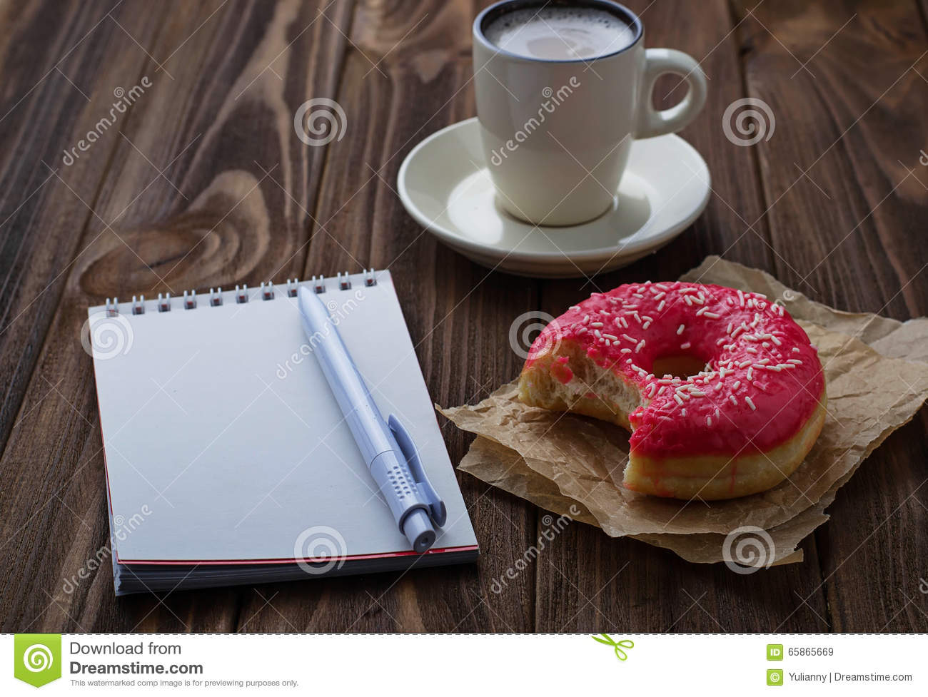 Bitten donut cup of coffee and notebook