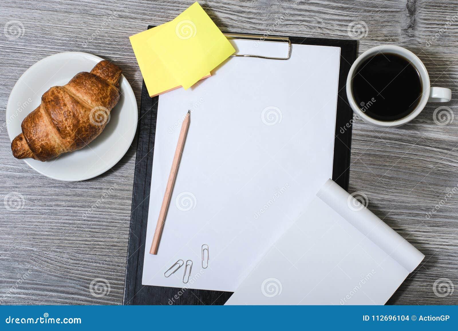 Biuro accessorise na drewnianym szarość stole: schowek, filiżanka coffe