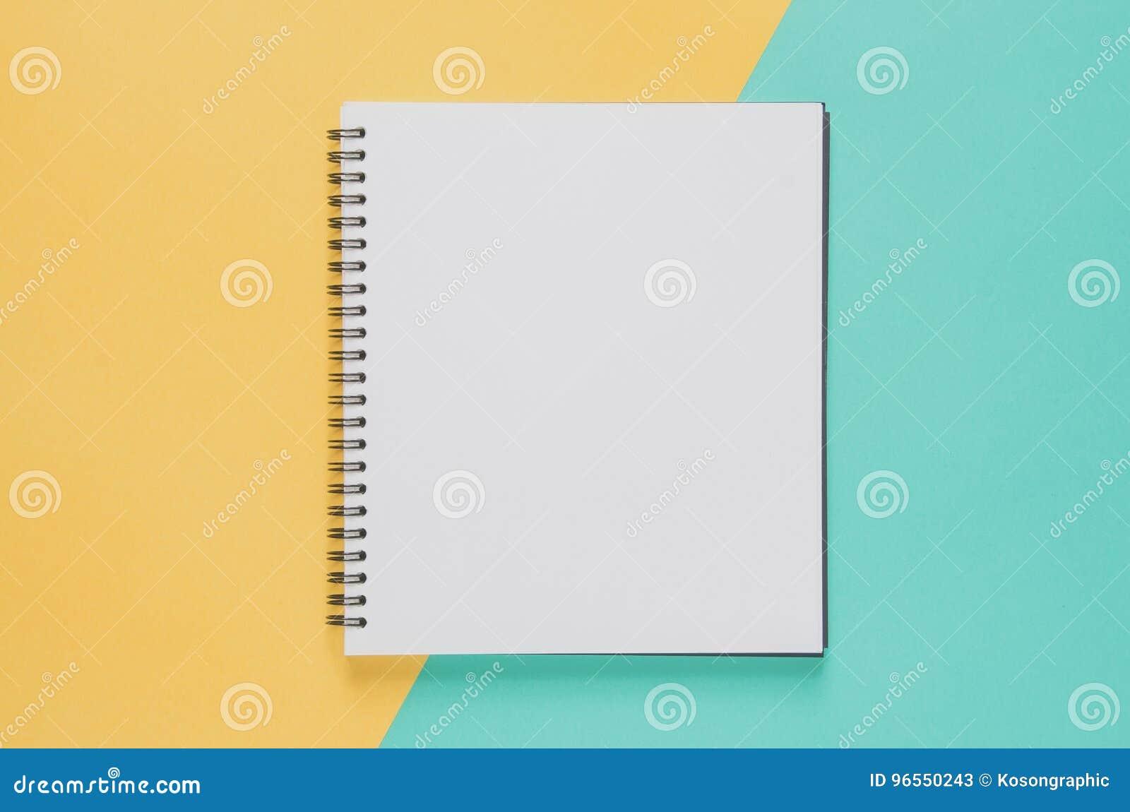 Biurowego miejsca pracy minimalny pojęcie Pusty notatnik na kolorze żółtym i b