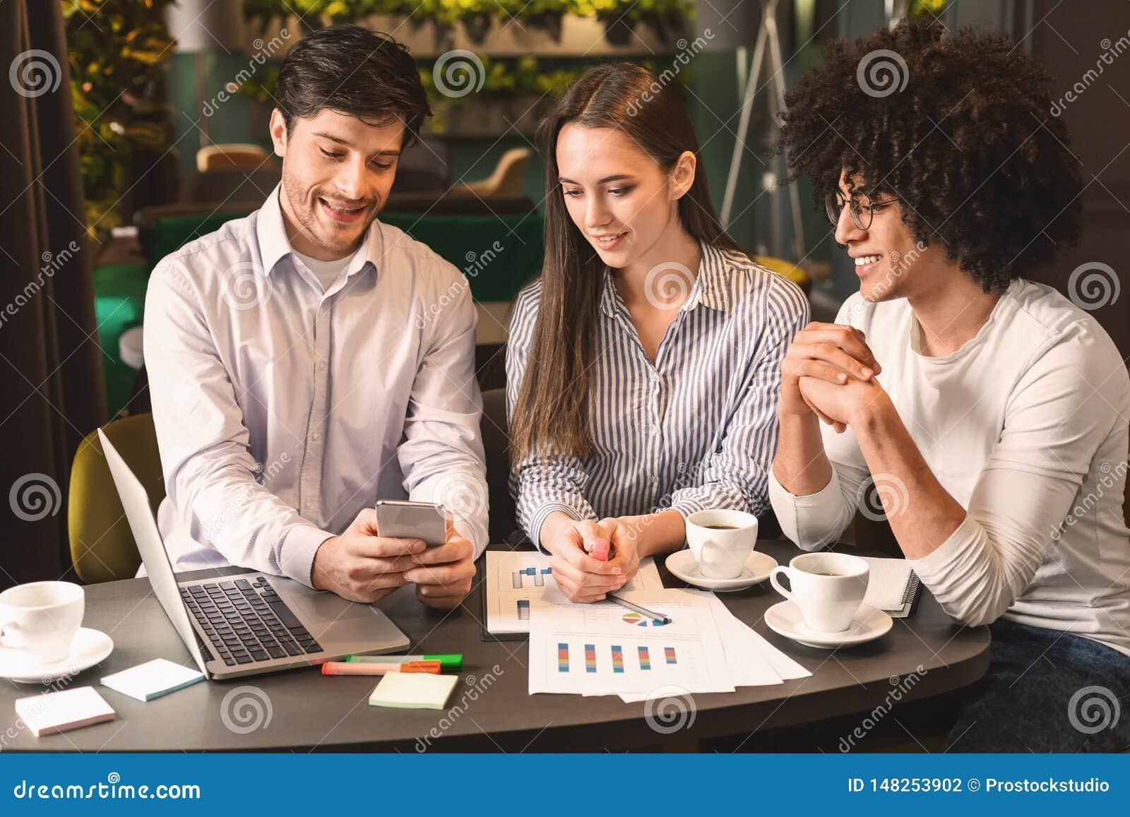 Biznes dru?yna na spotkaniu dyskutuje projekt z smartphone w kawiarni