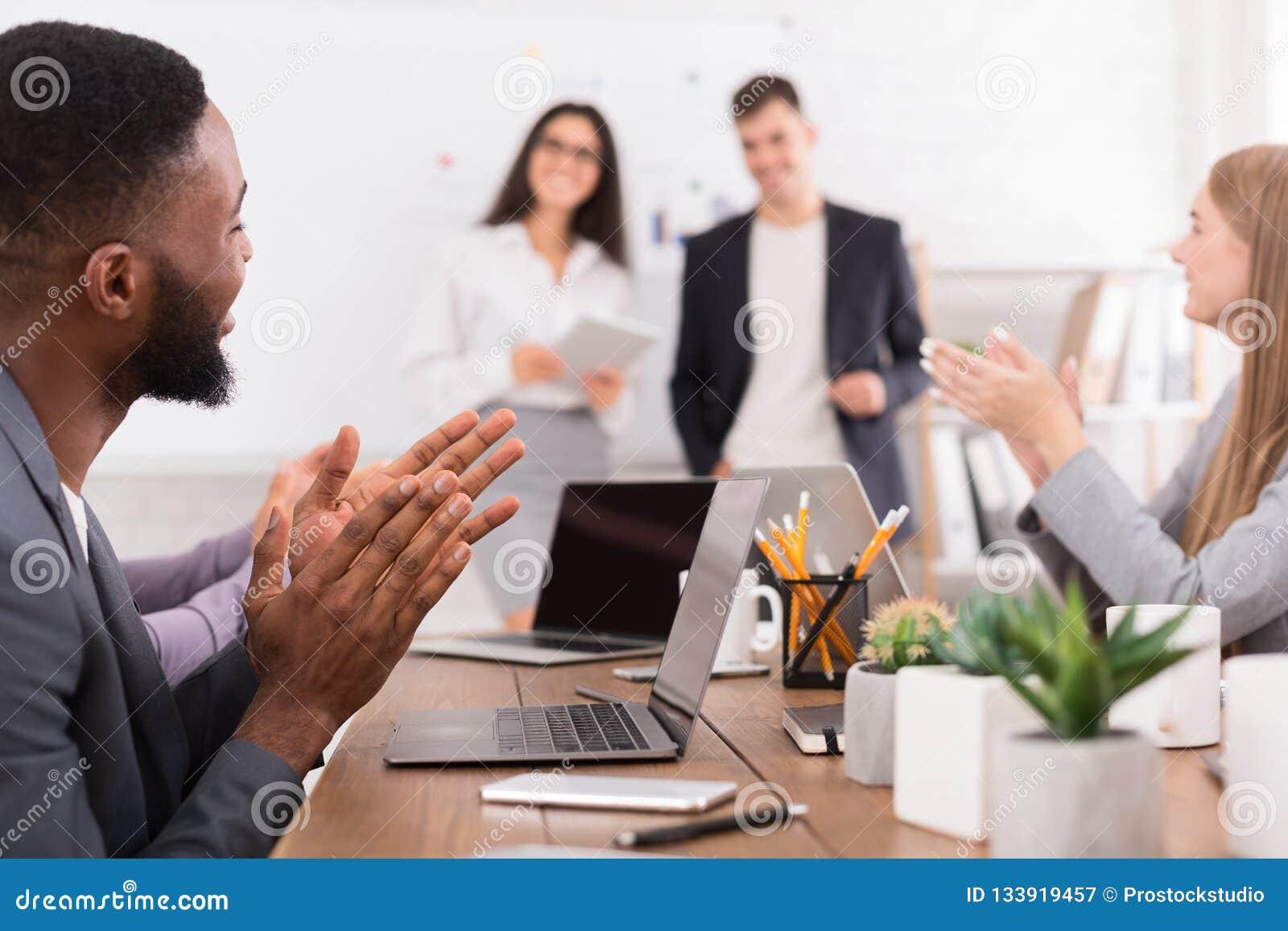 Biznes przewodniczy konferencyjnego biurko odizolowywającego nad biel Różnorodna drużyna oklaskuje mówców przy spotkaniem