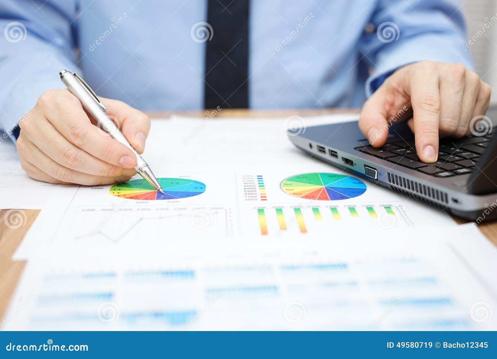 Biznesmen analizuje biznesowych dane i używa laptop