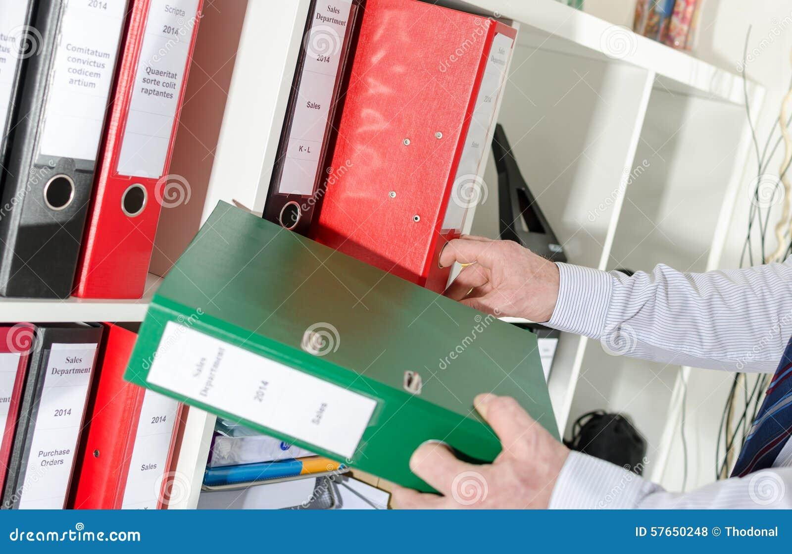 Biznesmen bierze segregatorów od półki
