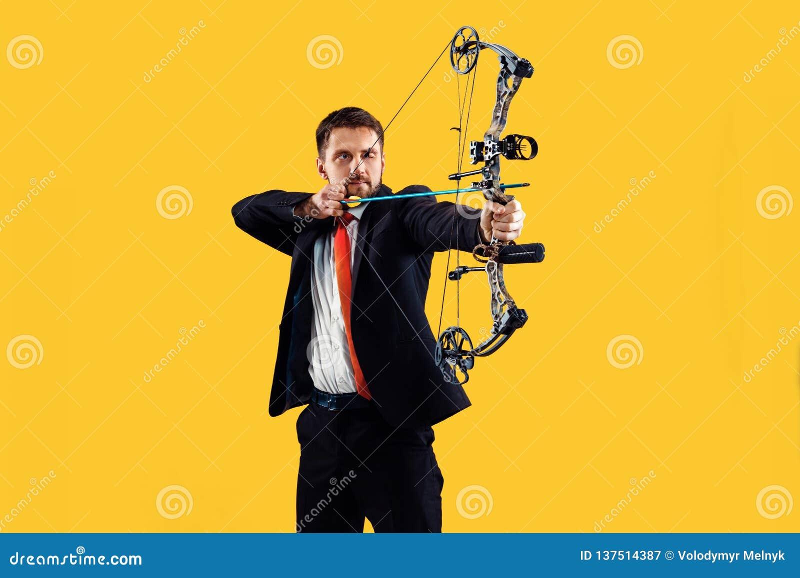Biznesmen celuje cel z łękiem i strzałą odizolowywającymi na żółtym tle,