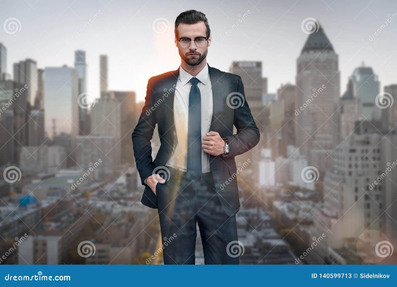 Biznesmen eleganckie Przystojny młody człowiek patrzeje daleko od przy kamerą utrzymuje jeden rękę w kieszeni w kostiumu podczas