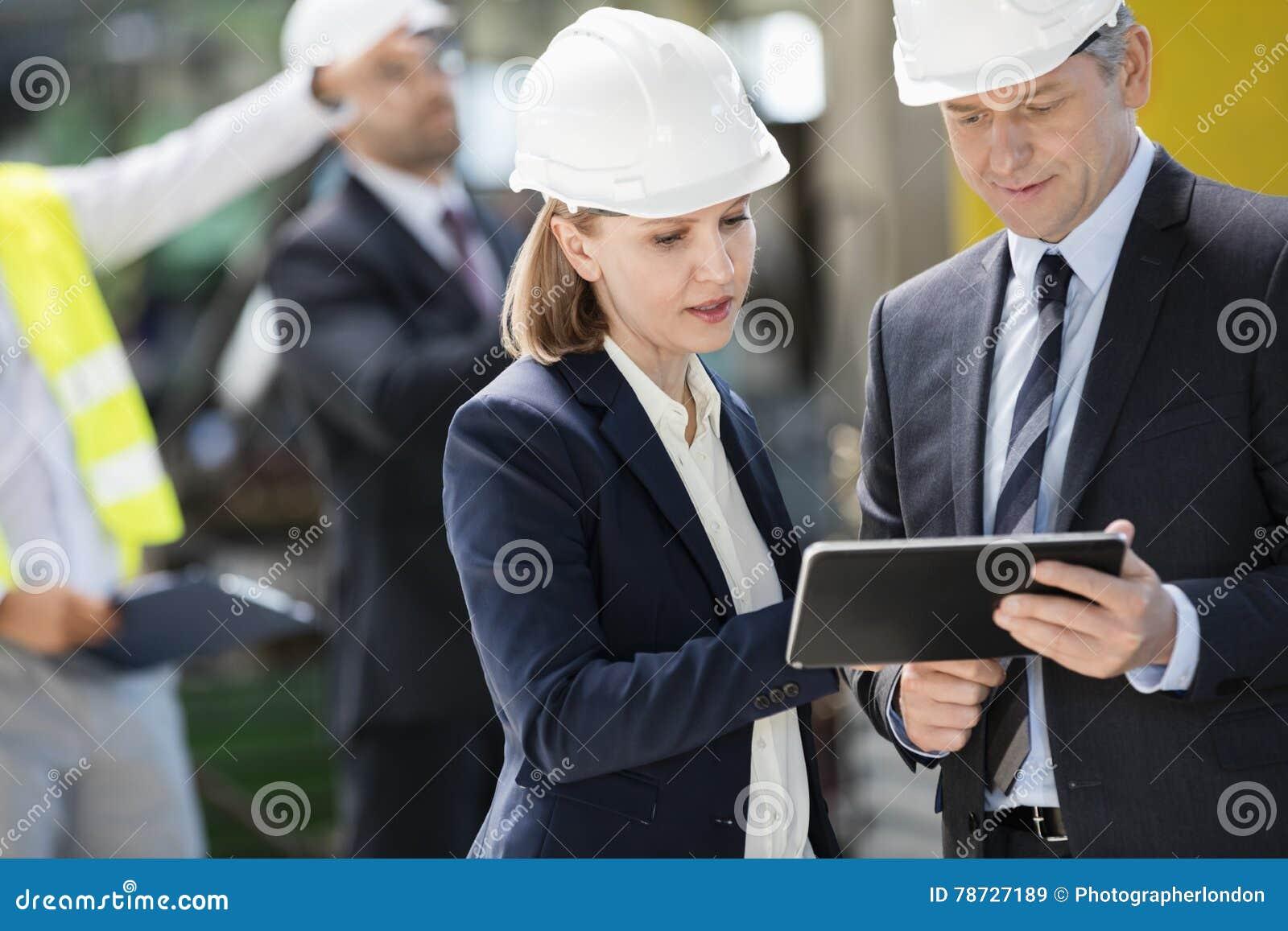 Biznesmen i bizneswoman używa cyfrową pastylkę z kolegami w tle przy przemysłem
