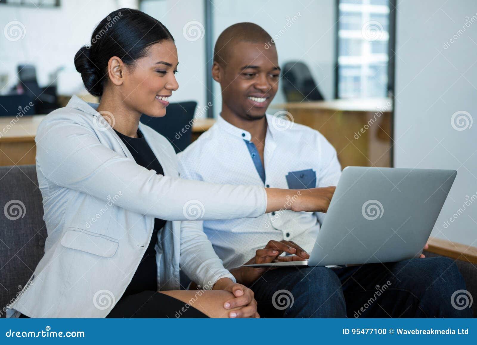 Biznesmen i kolega dyskutuje nad laptopem