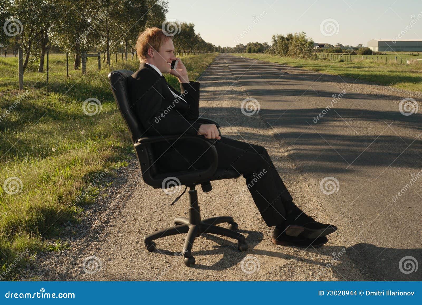 Biznesmen na bocznej drodze w krześle
