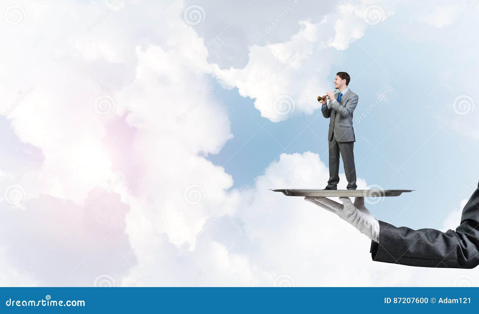 Biznesmen na metal tacy bawić się piszczałkę przeciw niebieskiego nieba tłu