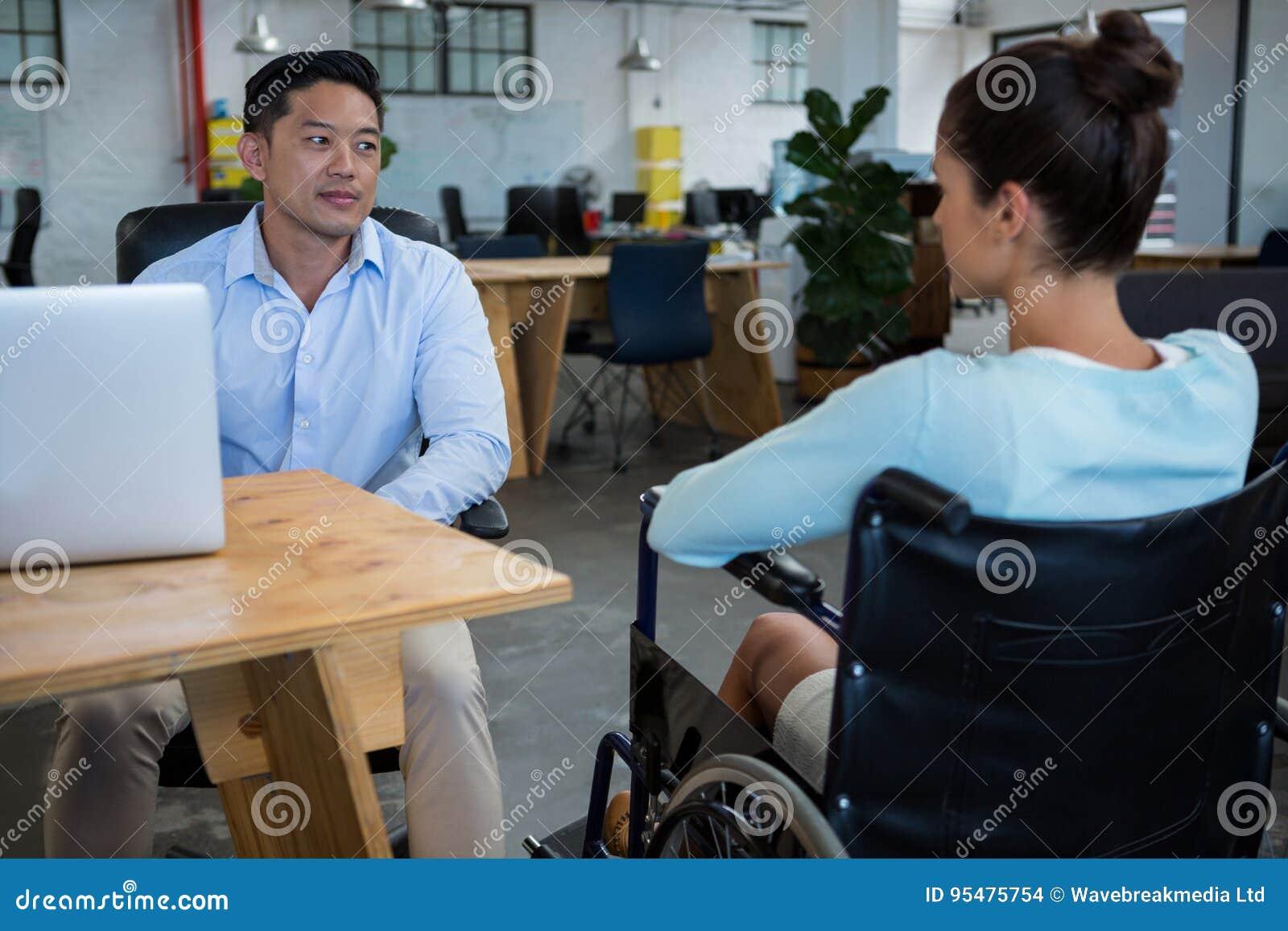 Biznesmen oddziała wzajemnie z niepełnosprawnym kolegą