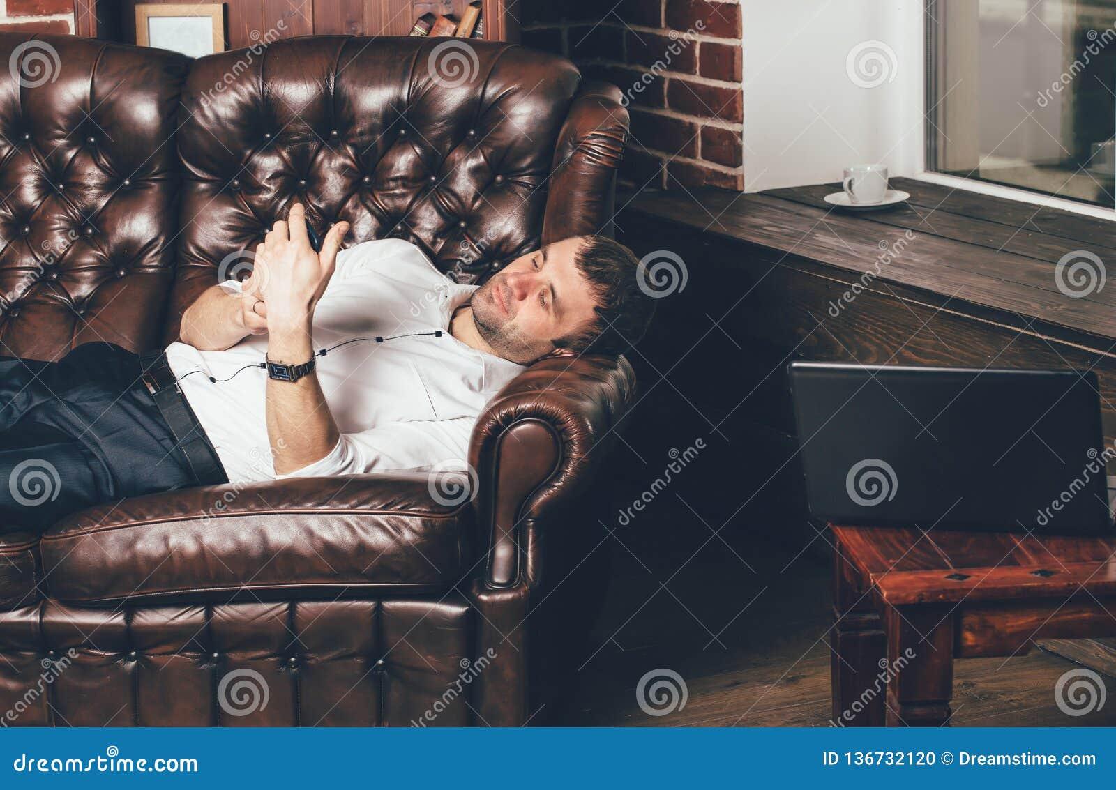 Biznesmen odpoczywa na rzemiennej kanapie blisko laptopu z filiżanką herbata w pokoju Mężczyzna trzyma telefon w jego ręce