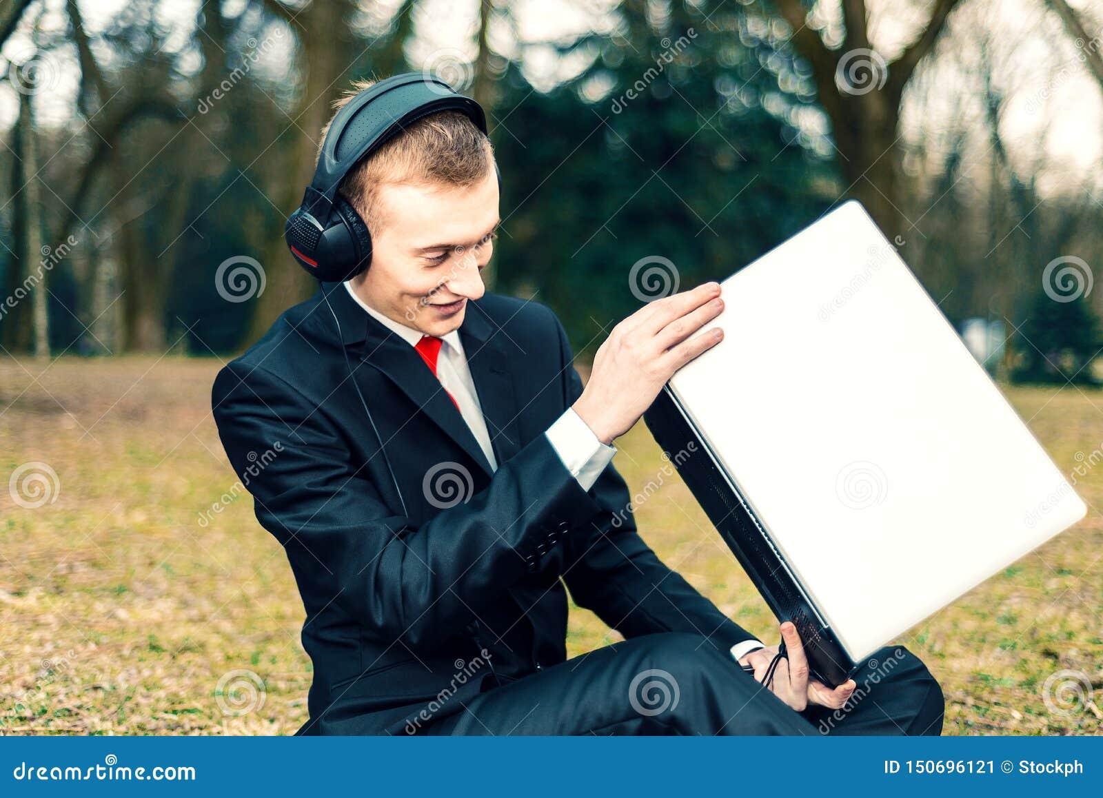 Biznesmen opowiada na laptopie w hełmofonach Internetowa komunikacja młody facet w kostiumu na naturze freelancer, odległy