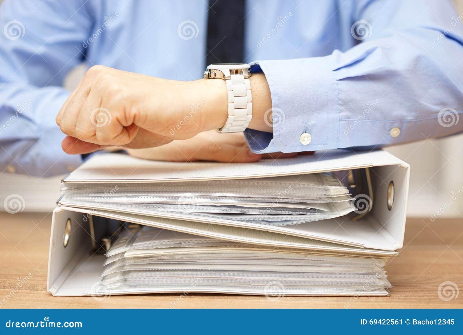 Biznesmen patrzeje na w z stertą dokumentacja na biurku