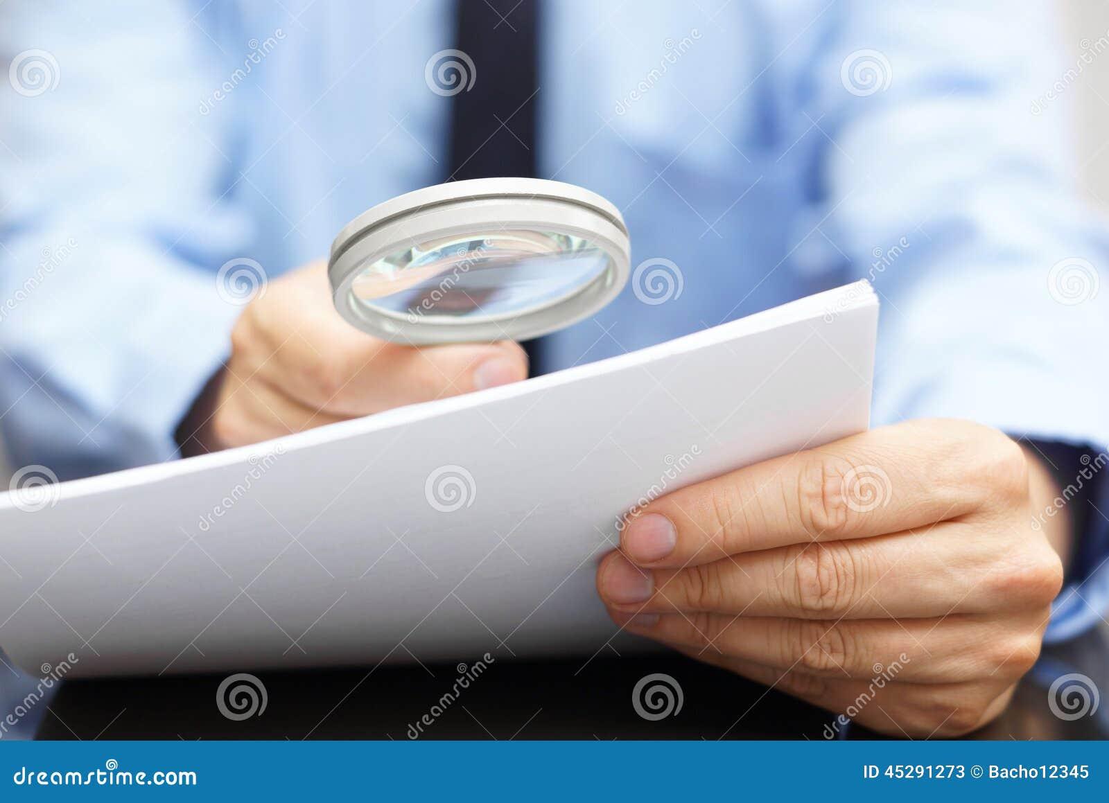 Biznesmen patrzeje przez powiększać - szkło skracać