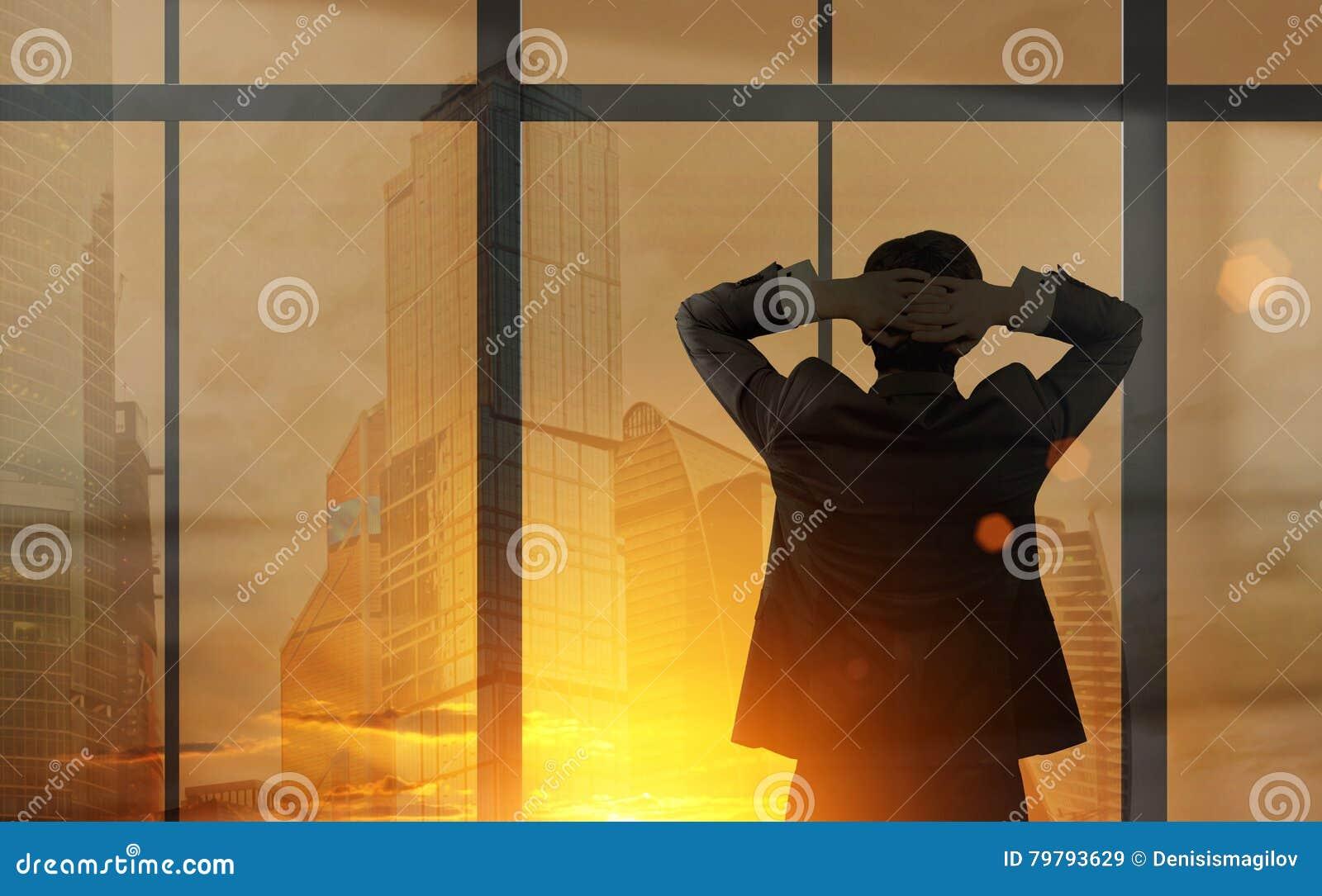 Biznesmen patrzeje z jego biurowego okno