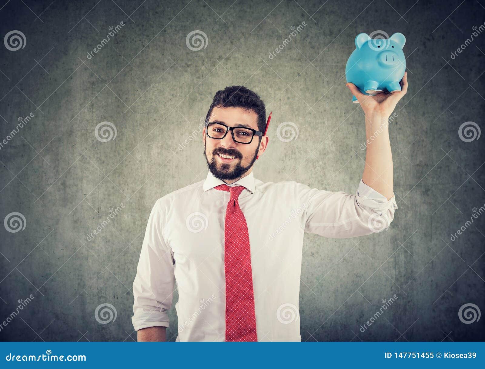 Biznesmen podtrzymuje prosiątko banka