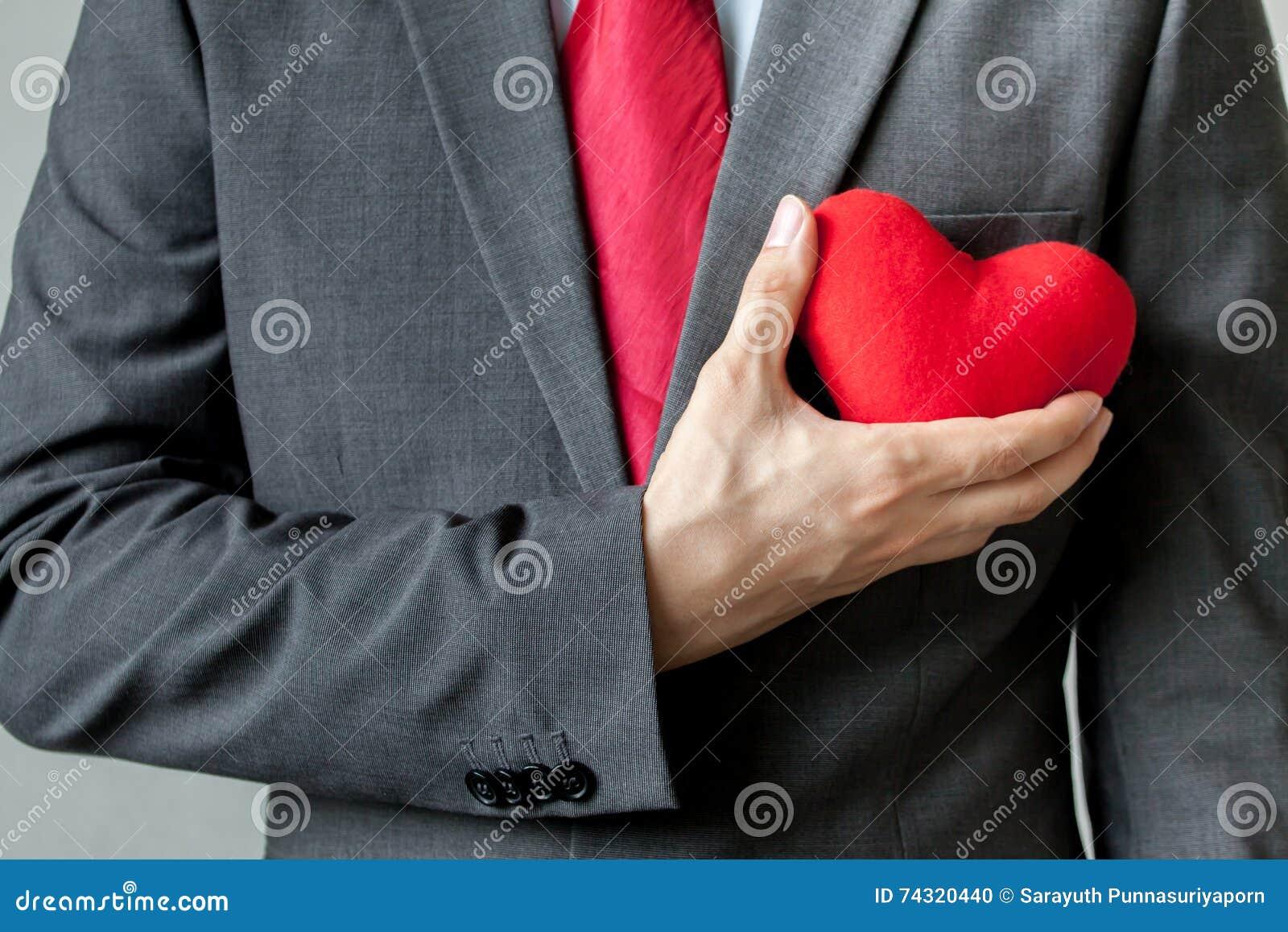 Biznesmen pokazuje współczucia mieniu czerwonego serce na jego klatce piersiowej